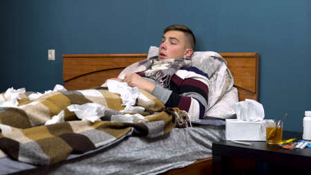 A young man sneezes. The guy is sick lying on the bed with a scarf around his neck. Paper scarves are scattered around