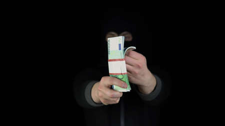 A man in a balaclava mask holds out a wad of euro. Bandit leafing through money. On a black background.