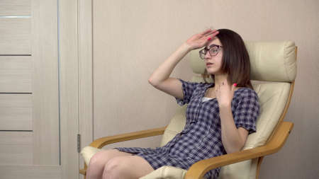 A young woman waves her hands because she is hot. A woman in a stuffy room sits on a chair. Banque d'images