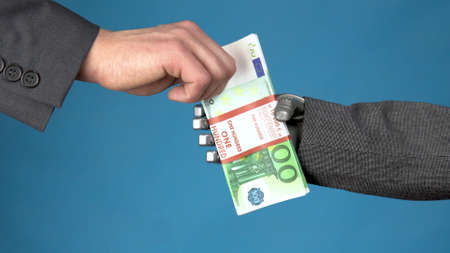 Cyborg businessman in a suit holds out a wad of euros to a man. Businessman takes money from a gray mechanical hand. Hands closeup on a blue background.