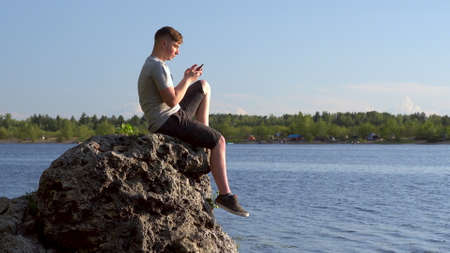 A young man sits on a stone by the river with a phone in his hands. The man is texting on his smartphone closeup.