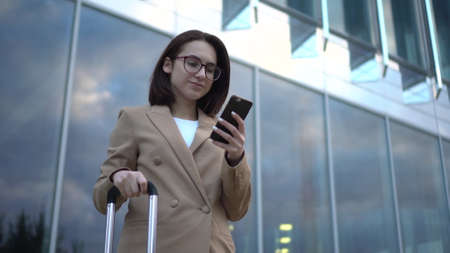 A young woman stands with a phone on the background of a business center.