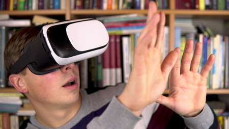 Young man in VR glasses in the library. A man with a VR helmet on his head examines and touches virtual reality. In the background are books on bookshelves. Book library