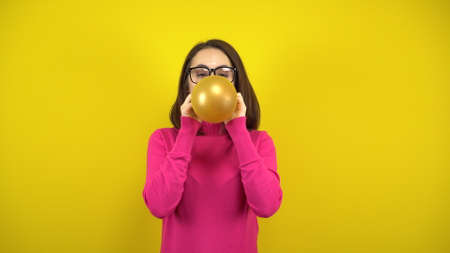 A young woman inflates a gold balloon with her mouth on a yellow background. Girl in a pink turtleneck and glasses.