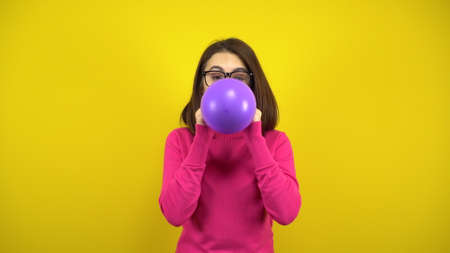 A young woman inflates a purple balloon with her mouth on a yellow background. Girl in a pink turtleneck and glasses. Banco de Imagens
