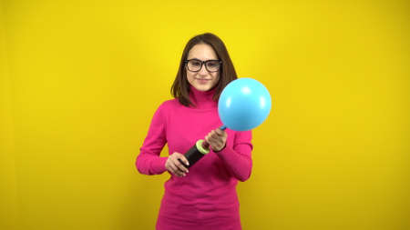 A young woman inflates a blue balloon with a pump on a yellow background. Girl in a pink turtleneck and glasses.