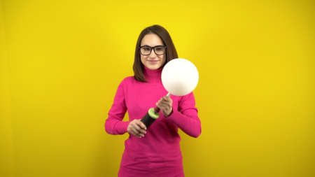 A young woman inflates a white balloon with a pump on a yellow background. Girl in a pink turtleneck and glasses.