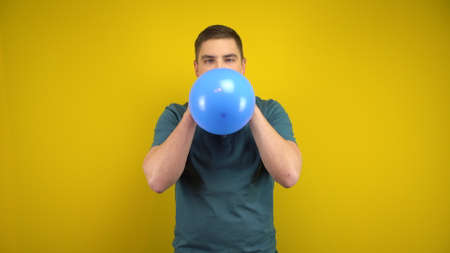 A young man inflates a blue balloon with his mouth on a yellow background. Man in a green polo. Banco de Imagens