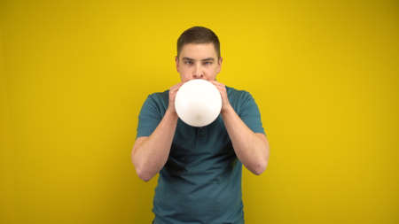 A young man inflates a white balloon with his mouth on a yellow background. Man in a green polo.