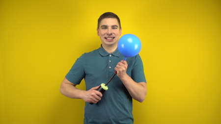 A young man inflates a blue balloon with a pump on a yellow background. Man in a green polo. Banco de Imagens