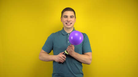 A young man inflates a purple balloon with a pump on a yellow background. Man in a green polo.