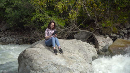 A young woman with glasses sits on a stone with a tablet in his hands in the mountains near the river. Travel to the mountains.