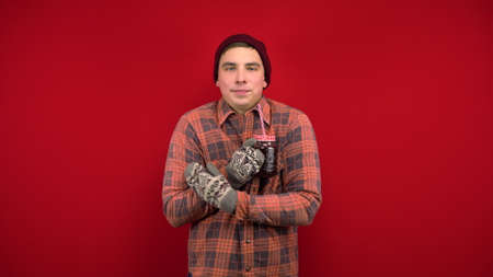 A young man in a hat and mittens keep freezing and drinking mulled wine. Shooting in the studio on a red background.