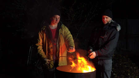 Two homeless young men are frying potatoes on a fire. Men stand at night near a barrel of fire and bask.
