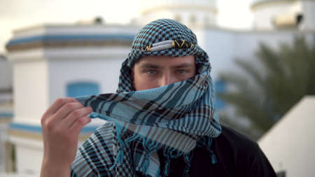 Young man in arabic handkerchief. The man covers his face. Against the background of the Arab house.