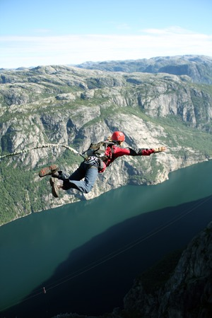 Jump off a cliff with a rope. photo