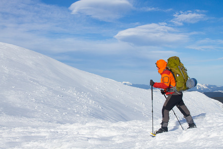 Winter hiking in the mountains on snowshoes with a backpack and tent. photo