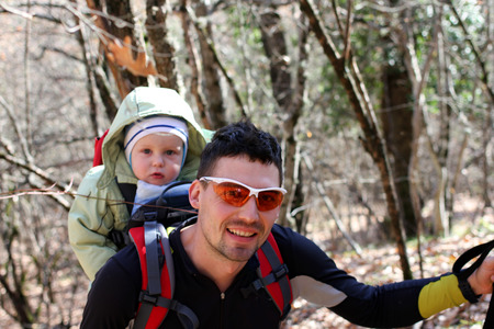 Father is hiking with the 1.5 year baby in baby carrier photo