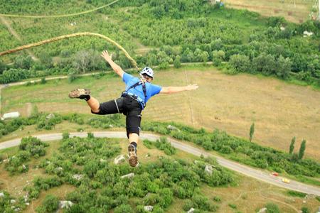 hombre cayendo: Saltar de un acantilado con una cuerda. Foto de archivo
