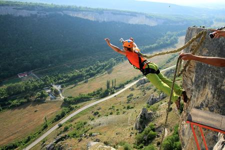 Springen van een klif met een touw.