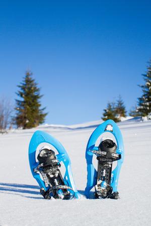 snowshoeing: Snowshoeing. Snowshoes in the snow.