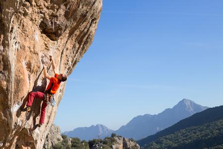 climbing: Escalador masculino joven colgando de un acantilado. Foto de archivo