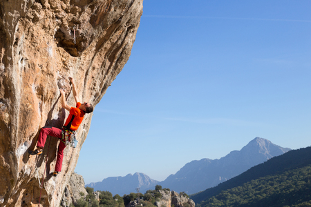 rock cliff: Young male climber hanging by a cliff.
