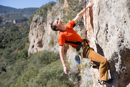 young male: Young male climber hanging by a cliff.