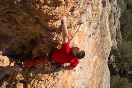 rock climbing: Young male climber hanging by a cliff.