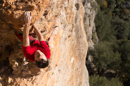 man climbing: Young male climber hanging by a cliff.