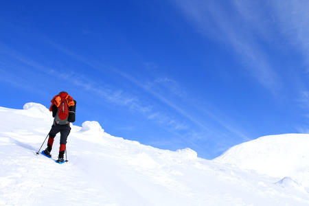 trekker: Winter hiking in the mountains on snowshoes with a backpack and tent. Stock Photo