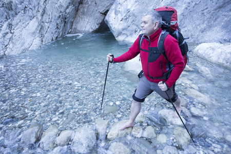 enters: Man enters the river in the canyon.