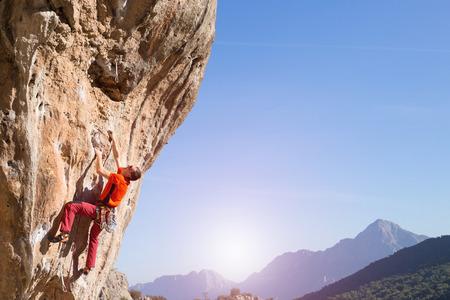 joven sube en un acantilado con una cuerda.