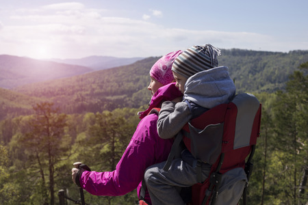 Mom walks in the forest with a child, a child in the children carry. Standard-Bild
