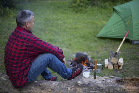 campsite: Man drinking coffee by the fire at a campsite on the river bank.