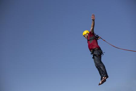 bungee jumping: Un hombre salta de un acantilado en el abismo.