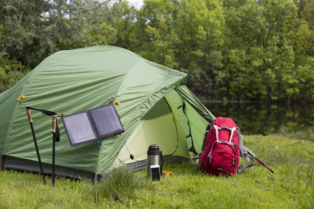 The solar panel attached to the tent. The man sitting next to mobile phone charges from the sun. Archivio Fotografico