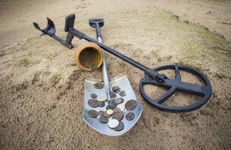 collected: Pot of gold coins collected with help of metal detector, green grass background.