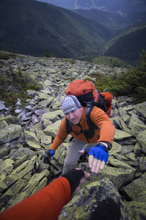 Mountain instructor handed someone a helping hand to the top of the mountain.