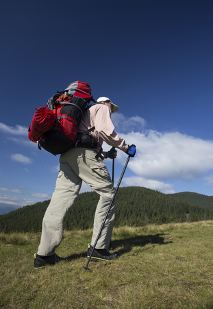 Summer hiking in the mountains with a backpack and tent.