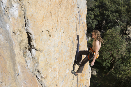 rappelling: Rock climber to climb the wall. Stock Photo