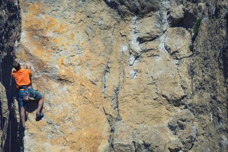 彼の次の手のために達するロック ・ クライマーを保持、ジョシュア ツリー国立公園。