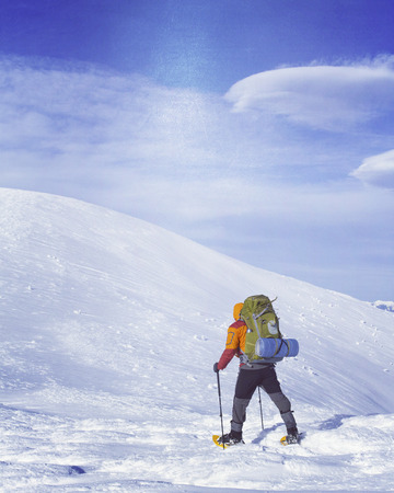 snowshoes: Winter hiking in the mountains on snowshoes with a backpack and tent. Stock Photo