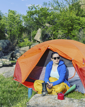 A girl is sitting near a tent in a campsite drinking coffee talking on the phone. Stock Photo