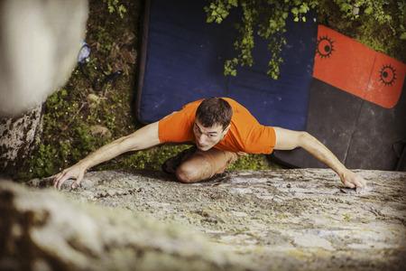Rock climber reaching for his next hand hold Joshua Tree National Park. Stock Photo