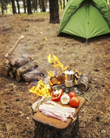 Camping in the forest. Preparation of breakfast at the stake. Stock Photo