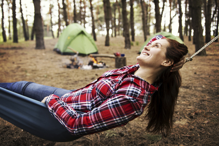 Camping in the forest. The girl sits in a hammock and looks at the fire.