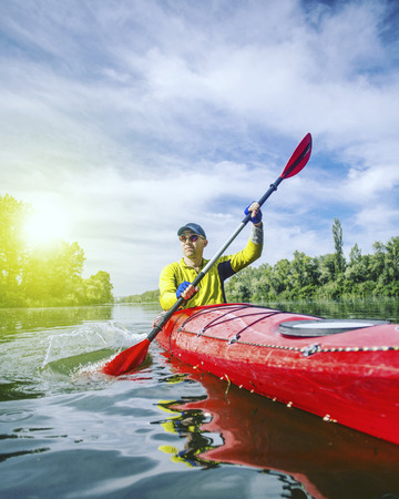 A man rafts on a kayak on the river in a sunny day. Stock Photo