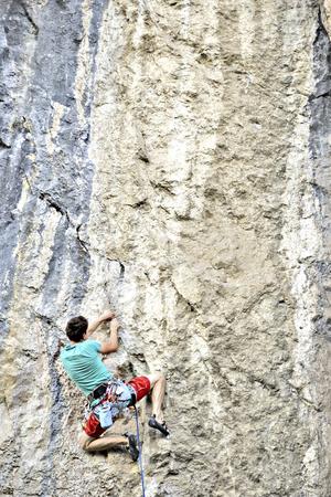 背景に広い谷と石灰岩の壁に登って若い男