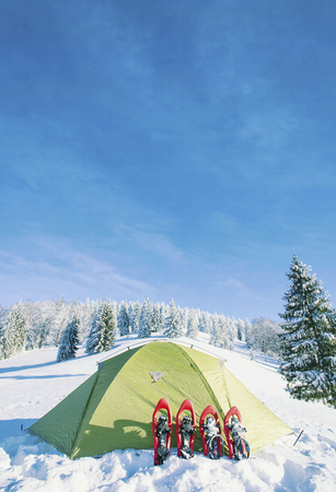The tent stands on a mountainside in the snow.
